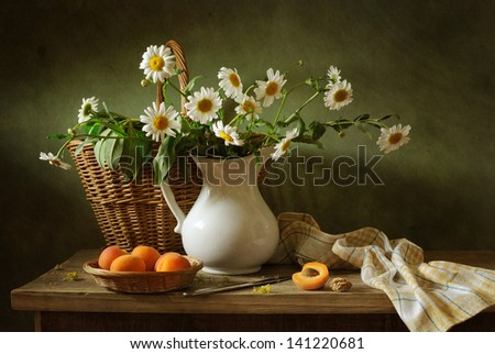 Still life with apricots and camomile flowers - stock photo
