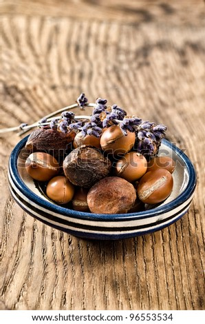 Still life with argan fruits in a dish over a wooden background - stock photo