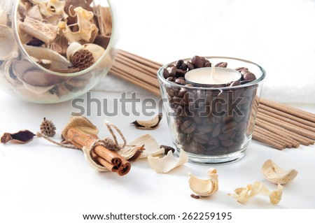 Still life with aroma candle in the glass with coffee beans, cinnamon, perfume sticks and ornamental dried flowers setting - stock photo