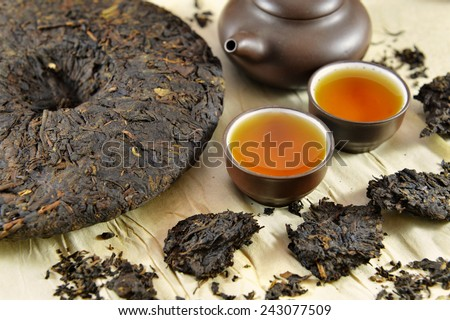 Still life with Asian pressed pu-erh tea and crockery tea set, clay pot and two small cups full of hot tea, on paper background  - stock photo