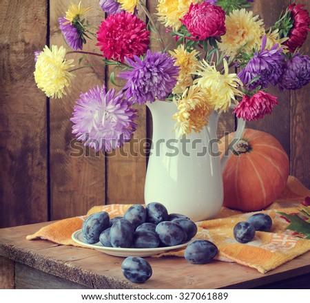 Still life with asters, pumpkin  & plums. A still life with an autumn bouquet. Autumn still life. - stock photo