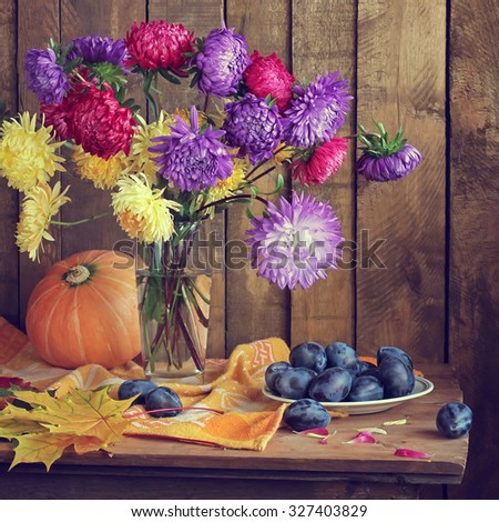 Still life with asters, pumpkin, plums and autumn leaves. A still life with an autumn bouquet. Autumn still life. - stock photo