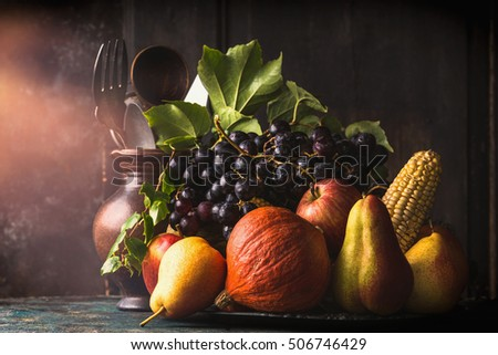 Still life with autumn fruits and vegetables: apples, pears, grapes, pumpkins, corn on the cob on dark rustic kitchen table at wooden background