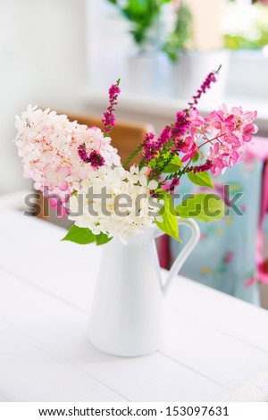 still life with autumnal flowers and berries on old white wooden table - stock photo