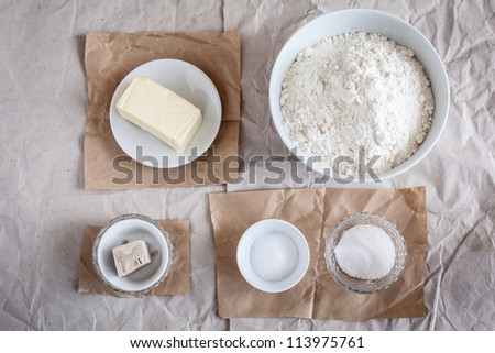Still life with baking ingredients like butter, yoast, flour, sugar and salt.