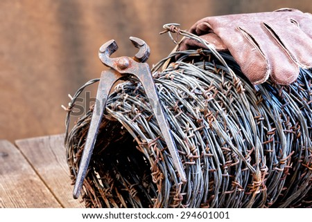 still life with barbed wire and old cutter - stock photo