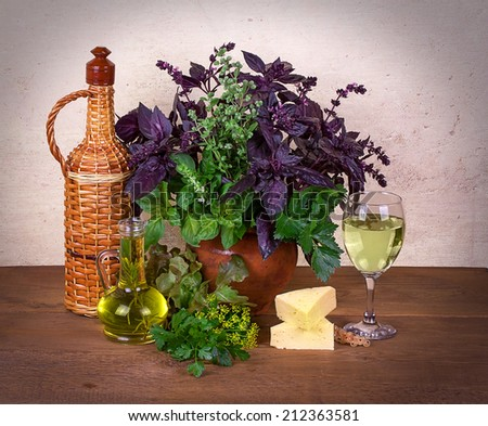Still life with basil, celery, dill, marjoram, parsley, lettuce; cheese and wine on wooden background - stock photo