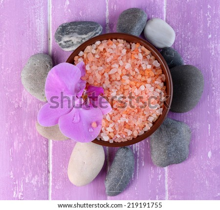 Still life with beautiful blooming orchid flower, sea salt and pebbles in bowl on color wooden background - stock photo