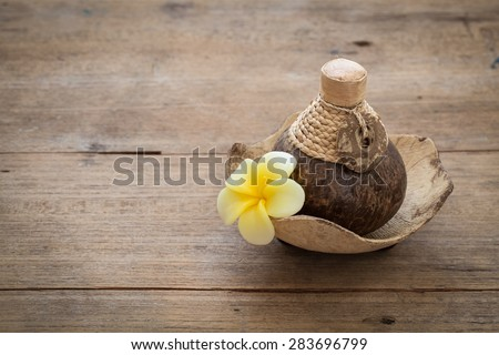 Still life with beautiful blooming orchid flower soap with oil treatment in coconut pot, spa treatment on bright background - stock photo