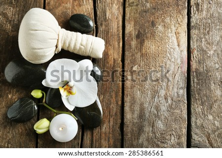 Still life with beautiful blooming orchid flower, spa treatment and pebbles, on wooden background - stock photo