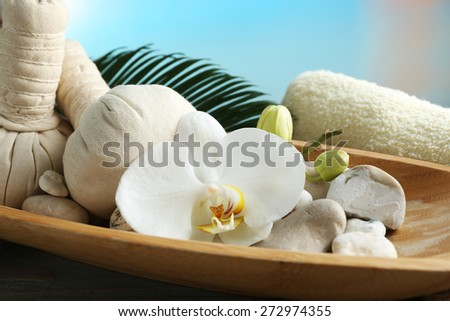 Still life with beautiful blooming orchid flower, spa treatment in bowl, on wooden table, on bright background - stock photo