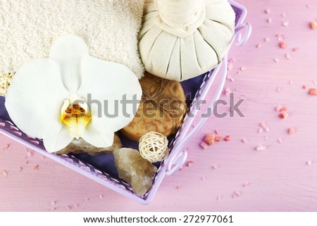 Still life with beautiful blooming orchid flower, spa treatment on tray, on color wooden background - stock photo