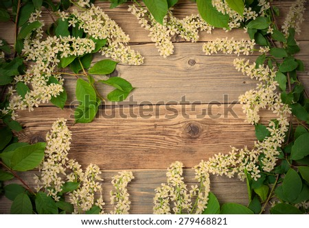 still life with beautiful branches of blossom bird cherry on vintage boards of antique table with copy space. instagram image filter retro style - stock photo