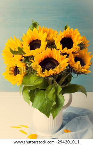 Still life with beautiful sunflowers bouquet in white vase on blue wooden background. Retro style toned. Greeting card concept. - stock photo