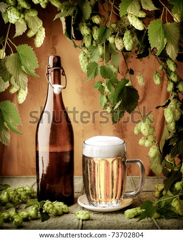 Still life with beer and hop-plant in vintage style - stock photo