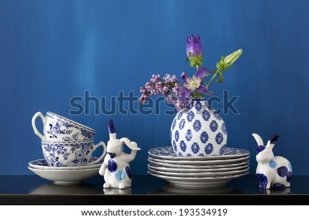 Still life with blue and white dishes, porcelain bunnies and flowers in a little vase