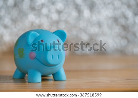 Still life with blue piggy back on wooden table and bokeh background, concept for saving