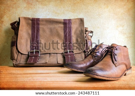 Still life with boots and bag on wooden table over grunge background