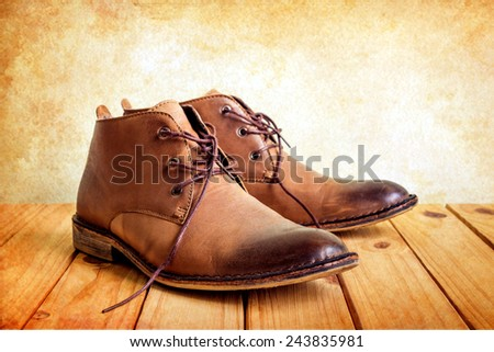 still life with boots on wooden table over grunge background