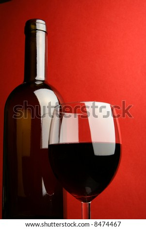 Still-life with bottle and glass over red background