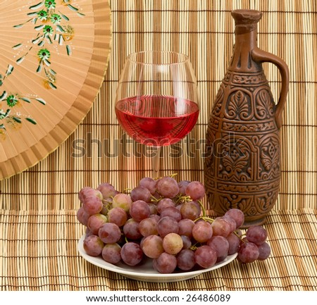 Still life with Bottle, bucket, goblet and grapes - stock photo