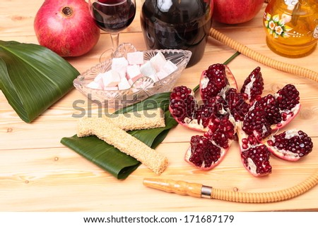Still-life with bottle of wine, garnet and sweets - stock photo