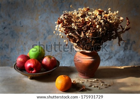 Still life with bouquet of dried roses in clay vase and fruits with grunge background - stock photo