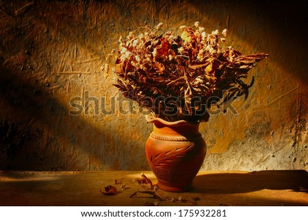 Still life with bouquet of dried roses in clay vase with grunge background - stock photo