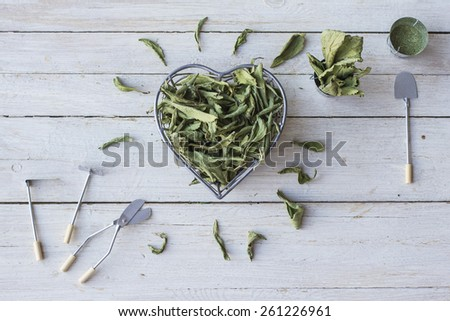 Still Life with  bowl in the form of a heart, full of dried stevia leaves. - stock photo