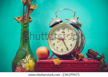 Still life with broken alarm clock, old glass vase with dead rose, egg, vintage box - stock photo