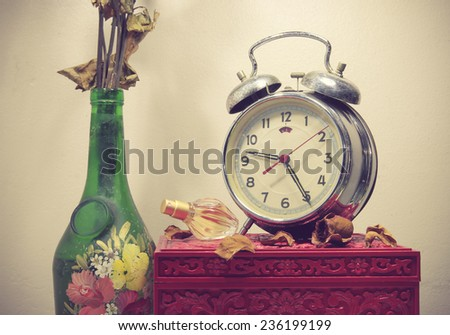 Still life with broken alarm clock, old glass vase with dead rose, perfume, vintage box, toned image. - stock photo