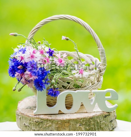 Still life with bunch of beautiful flowers in the basket and word Love - stock photo