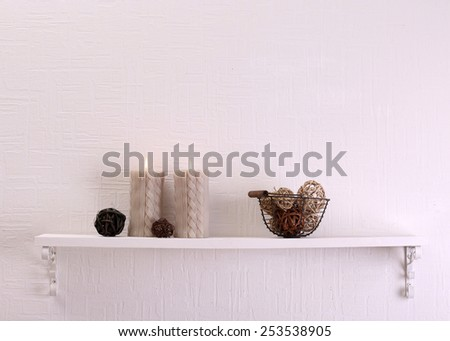 Still life with candles and dried balls on shelf on white wall background - stock photo