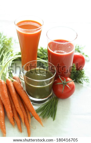 still life with carrots, carrot juice, tomatoes, and tomato juice  - stock photo