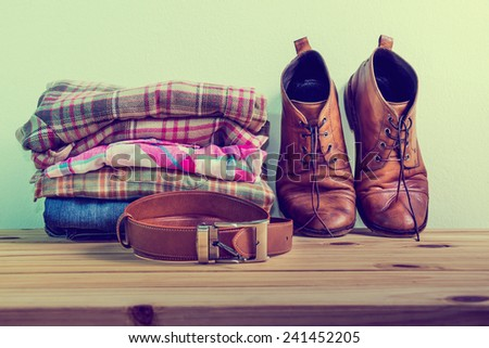 Still life with casual man on wooden table over grunge background - stock photo