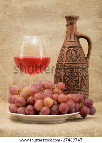 Still life with ceramic bottle, goblet and grapes