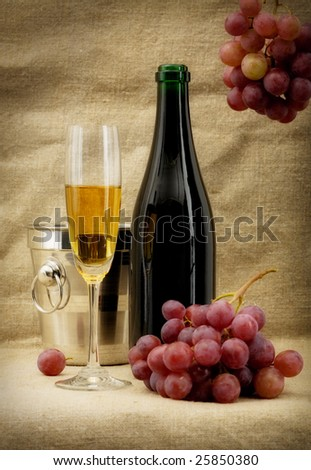 Still life with champagne bottle, bucket, goblet and grapes - stock photo