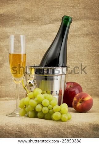 Still life with champagne bottle in bucket, goblet and fruits - stock photo