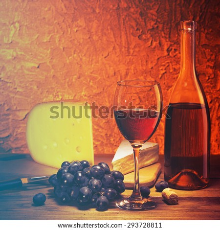 Still-life with cheese, grapes and glass and bottle of red wine. Filtered image:cross processed vintage effect. - stock photo