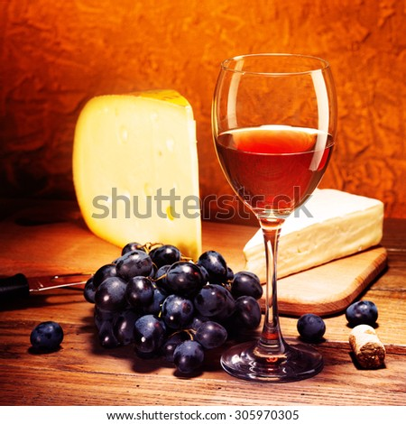 Still-life with cheese, grapes and glass of red wine.Filtered image: vintage effect. - stock photo