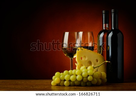 still life with cheese, grapes, red and white wine - stock photo