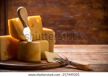 Still life with cheese on wooden board - stock photo