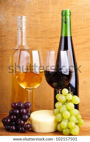 still life with cheese, wine and grapes on a vintage wooden background