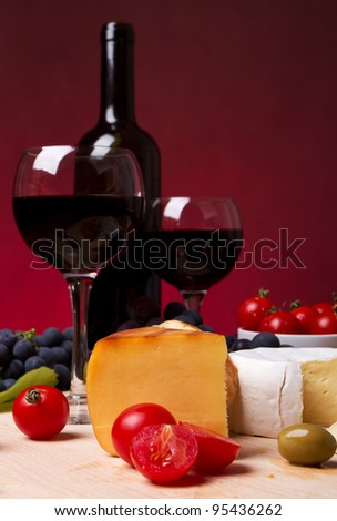 Still life with cherry tomato, red wine and cheese