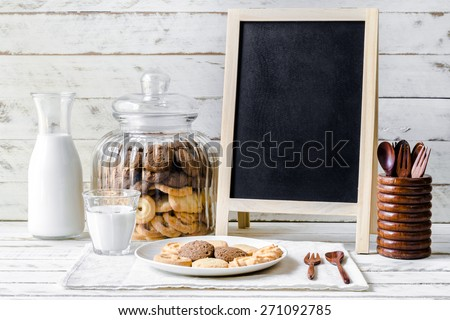 Still life with Chocolate chip and butter cookies with black board, wooden spoon and glass of milk on wood table background - stock photo