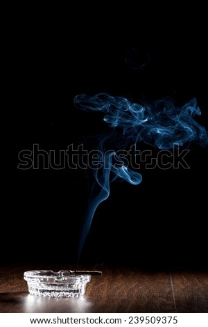 Still Life with cigar ashtray and smoke on a black background - stock photo