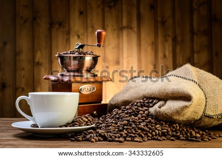 still life with coffee beans and old coffee mill on the wooden background