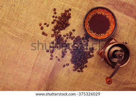 Still life with coffee beans, coffee mill  on the background of sackcloth. Top view. Horizontal toned image.