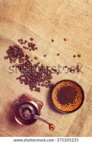 Still life with coffee beans, coffee mill  on the background of sackcloth. Top view. Toned image.