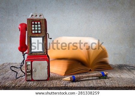 Still life with coin-operated phones, pencil and clock on wooden table over grunge background - stock photo